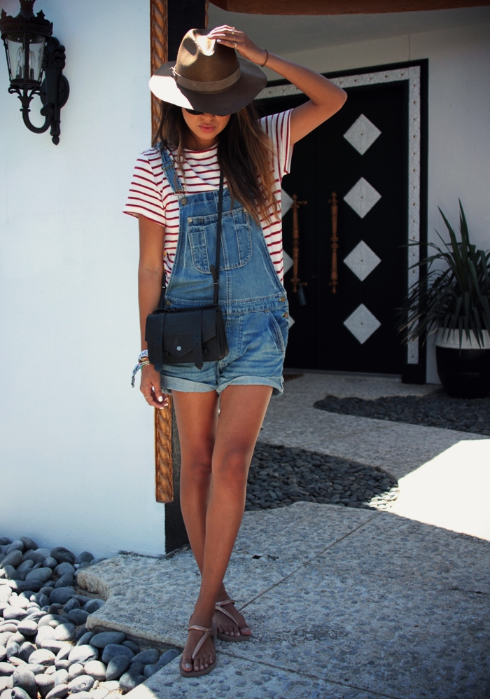 Sincerely Jules Is Wearing Overalls From American Eagle, Striped T-Shirt From Hye Park And Lune, Bag From Proenza Schouler, Hat From Emporio Armani And Sandals From Havaianas