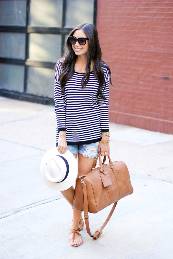 Kat Tanita is wearing a black and white striped top from Joie, denim shorts from Rag & Bone, bag from Sole Society, sandals from K. Jacques, hat from J. Crew and sunglasses from Celine