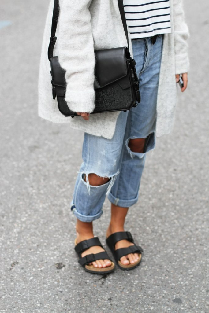 Mija is wearing a grey mohair cardigan from Acne Studios, ripped boyfriend jeans from Citizens of Humanity, bag from Alexander Wang, striped tee from NoName and black Birkenstocks