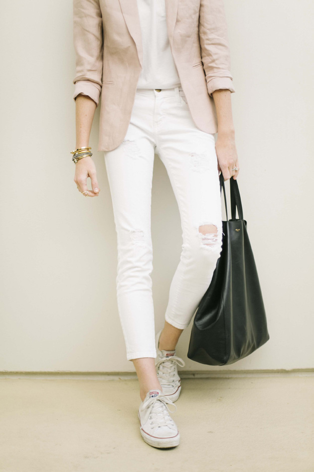 Samantha Hutchinson Is Wearing A T-Shirt From Everlane, Distressed White Jeans From Current/Elliott, Blazer From Joie, Sneakers From Converse And Tote From Celine