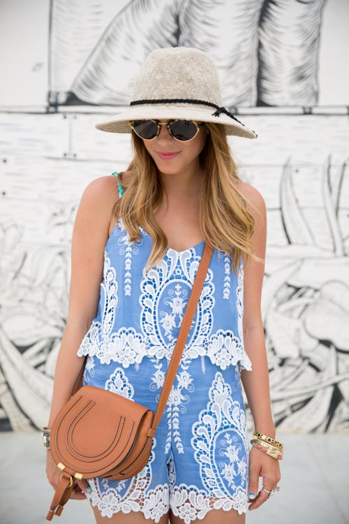 Gal Meets Glam Is Wearing Light Blue And White Lace Romper From Dolce Vita, Tan Bag From Chloe, Sunglasses From Illesteva Sunglasses And The Beige Hat Is From The Free People
