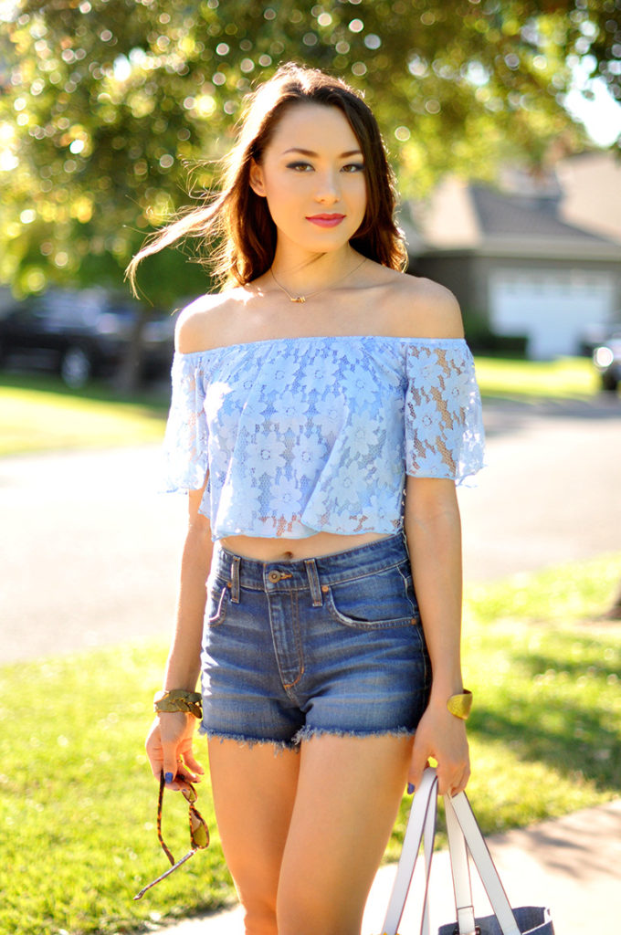 Jessica R is wearing a pale blue floral lace top from Sheinside and high waist denim shorts