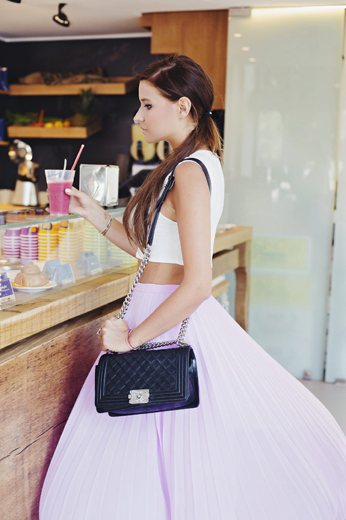 Veronica Ferraro is wearing a pale purple pleated skirt from ASOS, white crop top from Forever21 and a boy bag from Chanel