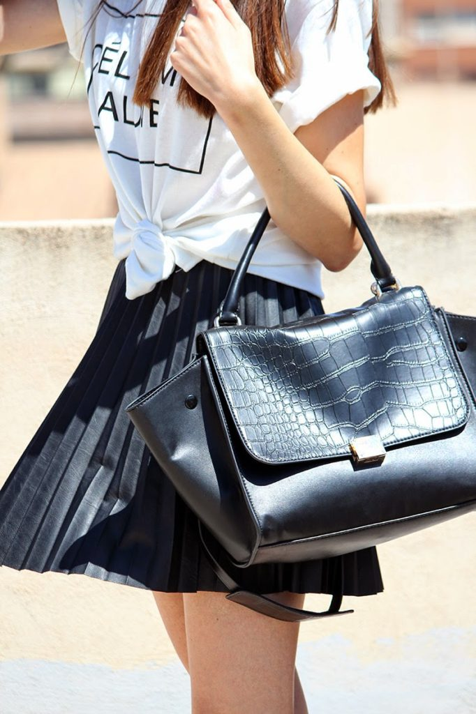 Angeles Y Diablillos Is Wearing A T-Shirt From Sheinside, Black Skirt With Pleats From Stradivarius, And Bag From Oasap