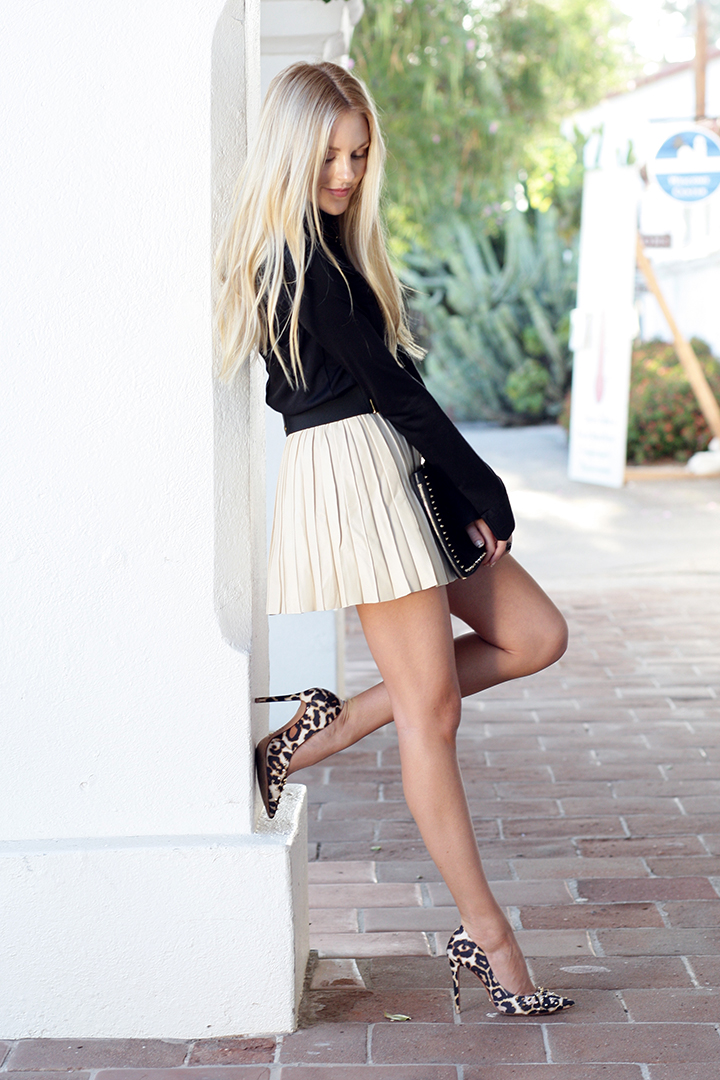 Peace Love Shea Is Wearing A Black Top From Balenciaga, Beige Pleated Skirt From Parker And Leopard Print Shoes From Schutz