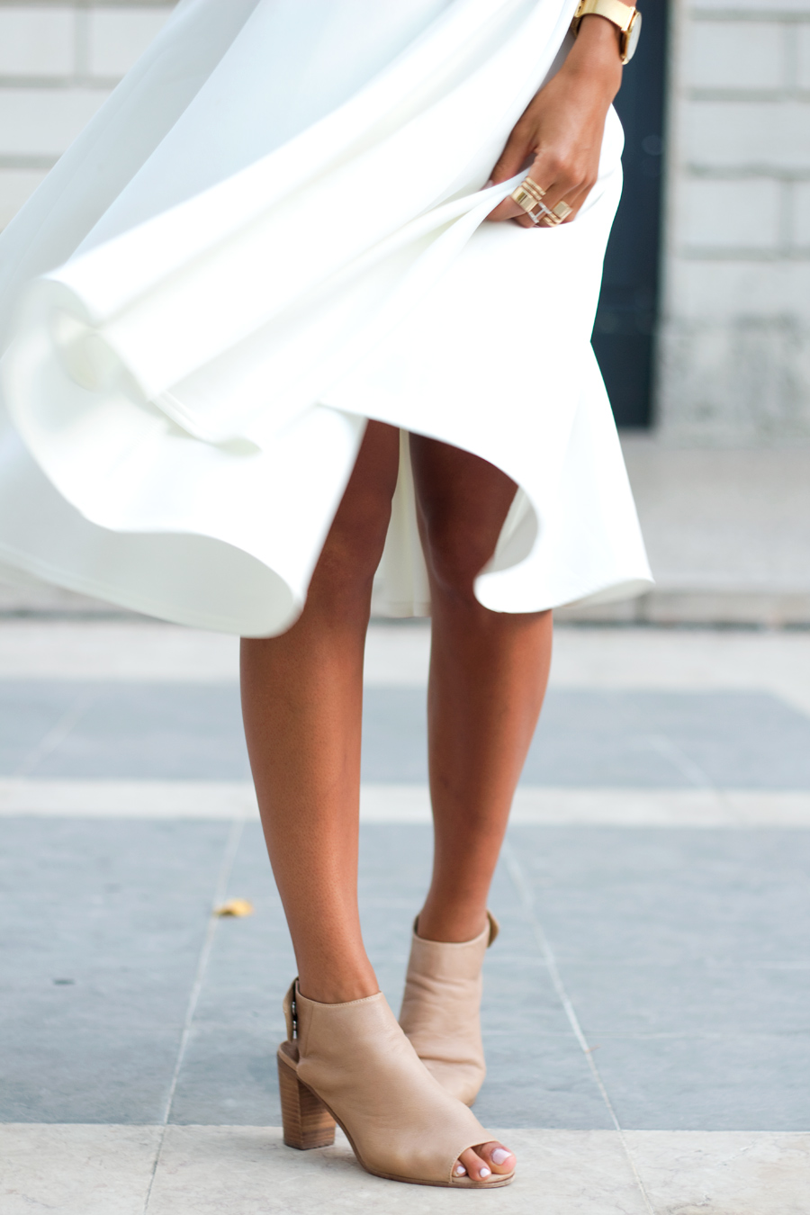 Kayla Seah is wearing a white skirt from ASOS and shoes from Steve Madden