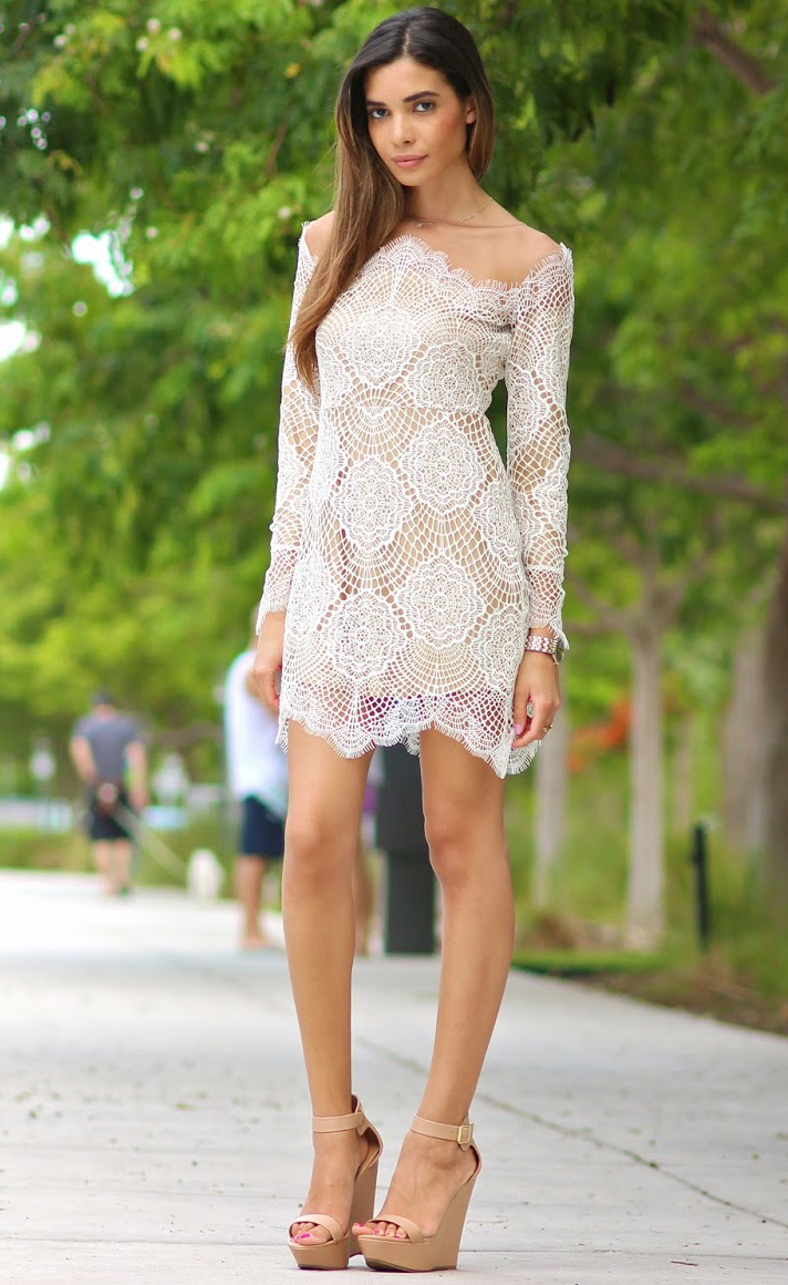 Jasmine Tosh is wearing a white lace dress from For Love & Lemons