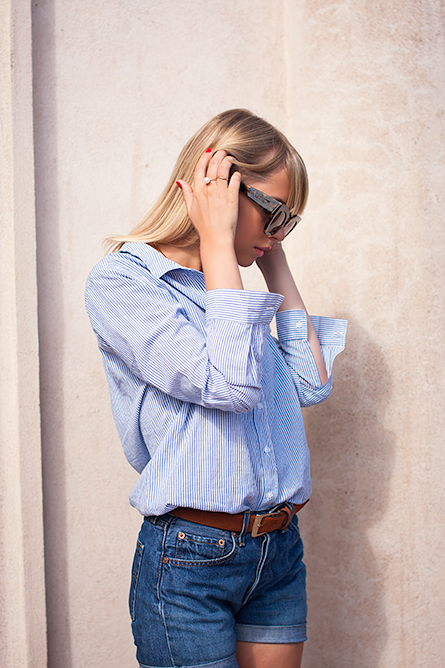 Charlotte Hellberg is wearing a striped boyfriend shirt from BikBok, shorts from Levi's and the sunglasses are from Karen Walker