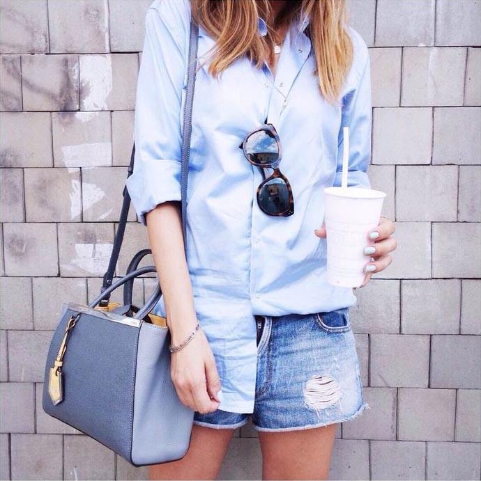 Unknown fashion blogger wearing a baby blue boyfriend shirt, denim cut offs and bag Via Scent Of Obsession