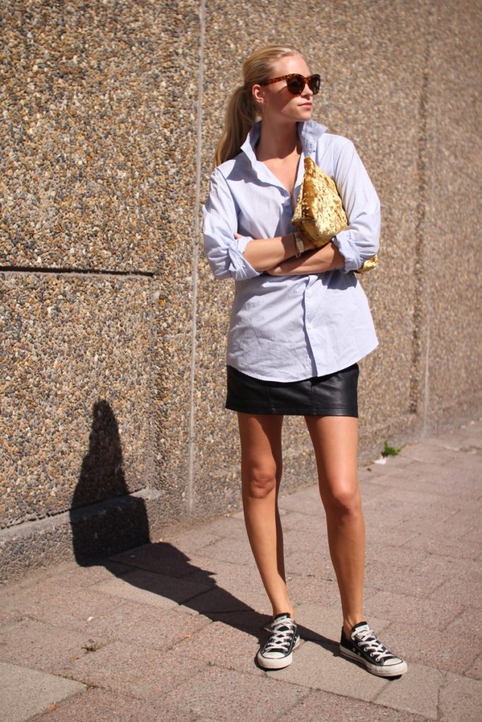 Tine Andrea is wearing a light blue boyfriend shirt, leather skirt and black converse