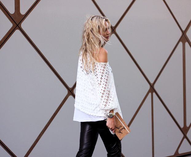 Anouk Yve is wearing a white eyelet shirt and leather trousers from Ganni