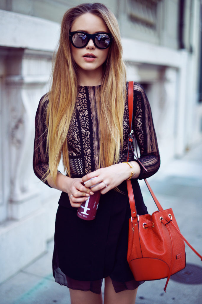 Kristina Bazan is wearing a black lace dress from Three Floor, red bag from Gucci and mirrored sunglasses from Sonya Rikiel