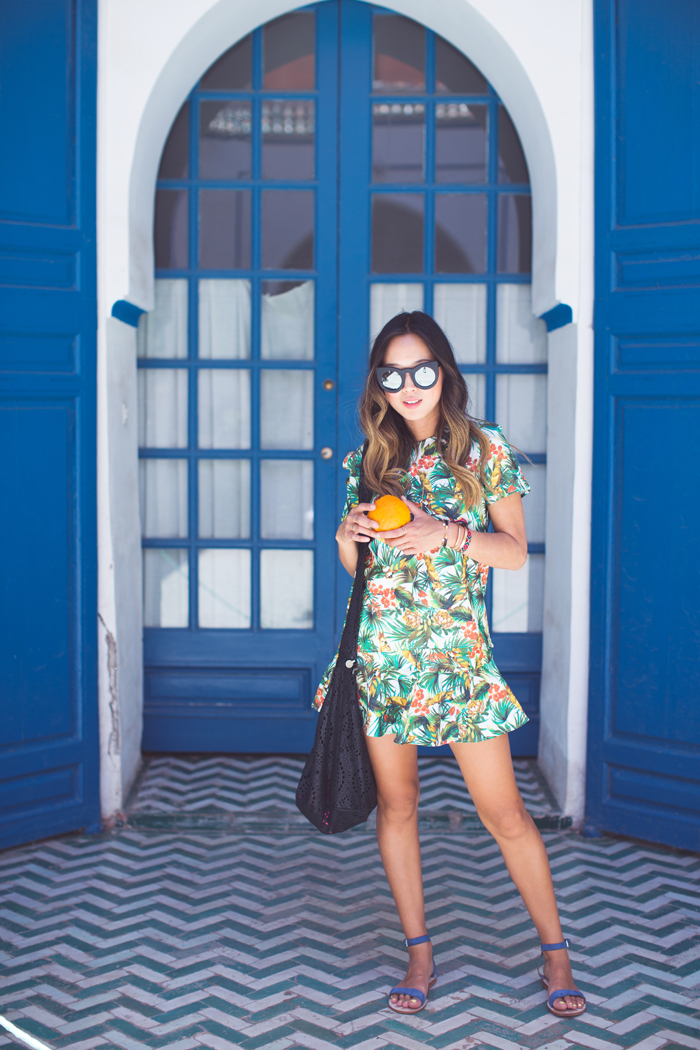 Aimee Song is wearing tropical print top and skirt from Fifth Label, sandals from Cornetti, bag from Camilla Coin, and mirrored sunglasses from Valley Eyewear