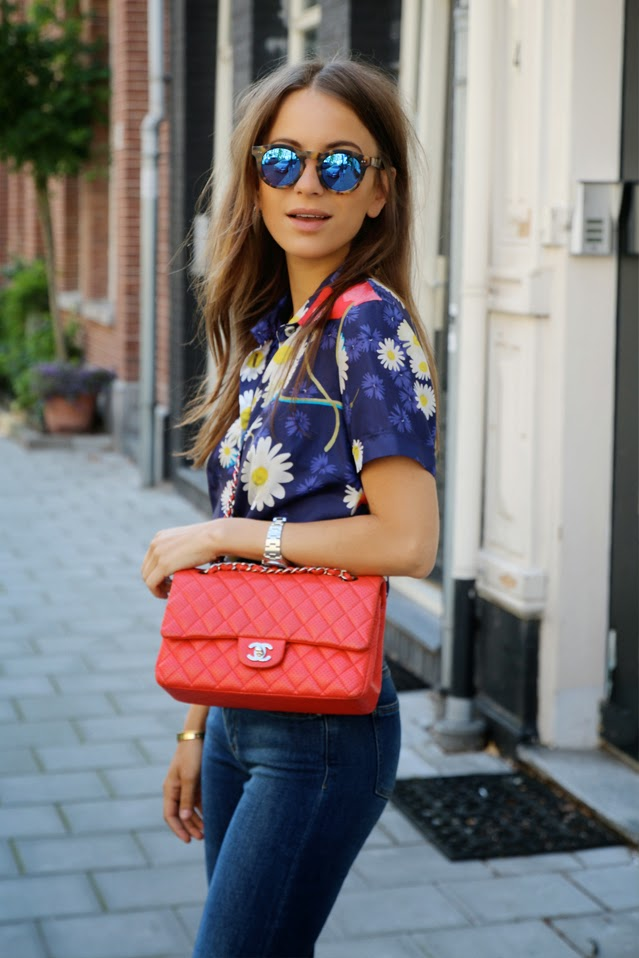 Lizzy Van Der Ligt is wearing a floral shirt from Dolce & Gabbana, jeans from Acne, bag from Chanel, and mirrored sunglasses from Capri People