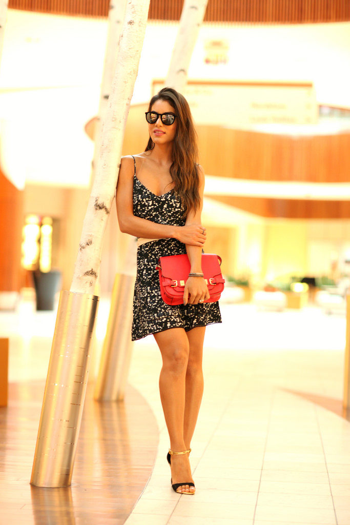 Camilla Coelho is wearing a dress from Sunday Best, sandals from Carmen Steffens, mirrored sunglasses from Rayban and the red bag is from Vince Camutto