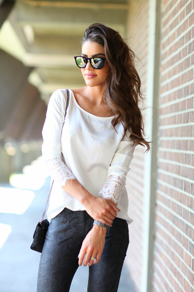Camila Coelho is wearing a lace trim blouse, snake print leggings and mirrored sunglasses from Amaro