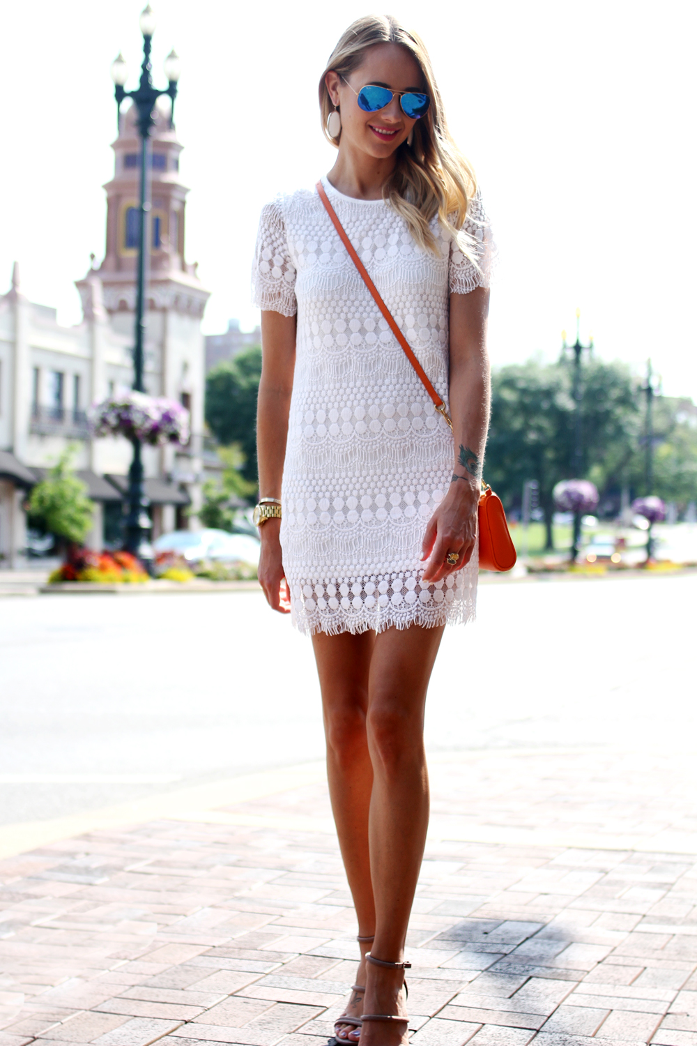 Amy Jackson is wearing a white short sleeve lace dress from Sheinside, bag from Gigi New York, shoes from Forever21 and blue mirrored sunglasses from RayBan
