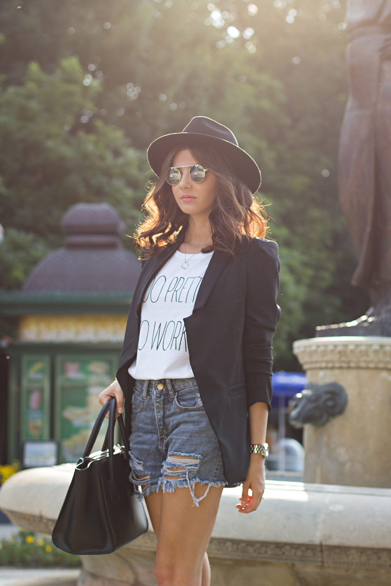 Larisa Costea is wearing denim shorts from Sheinside, T-shirt from Maison F, black blazer from Zara, hat and mirrored sunglasses from ASOS