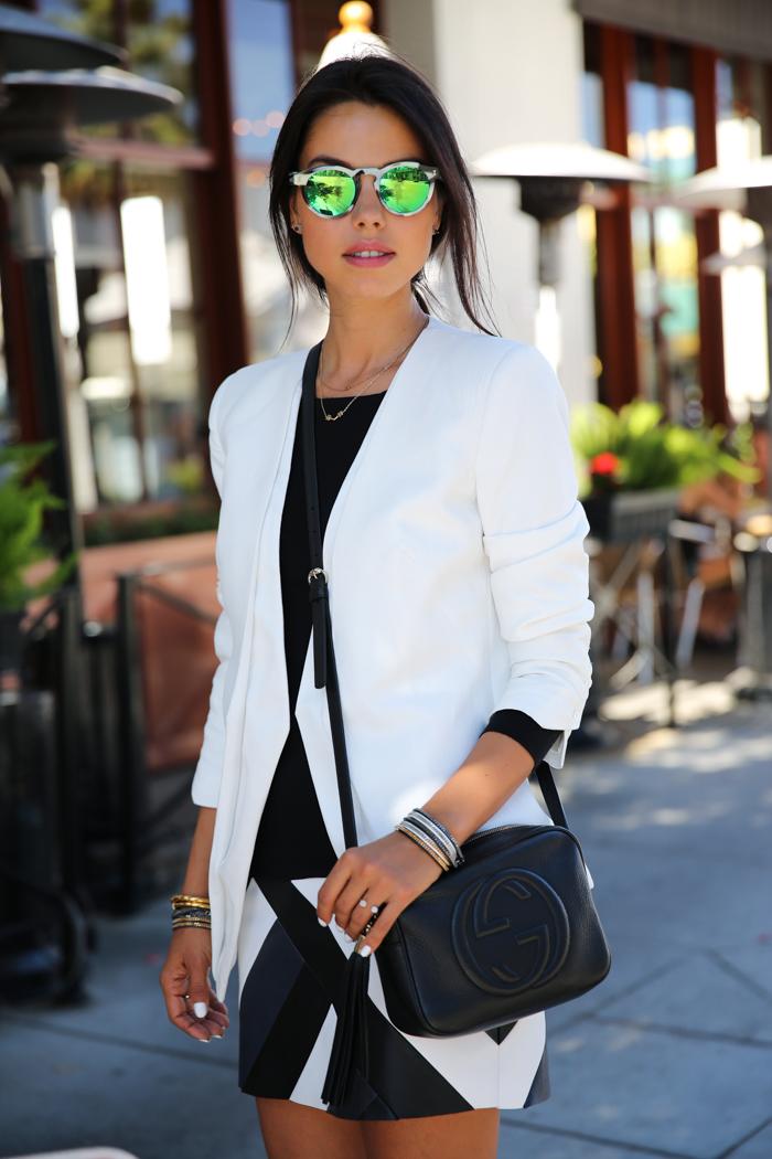 Annabelle Fleur Is Wearing Mirrored Sunglasses From Illesteva Leonard, White Blazer And Black And White Skirt