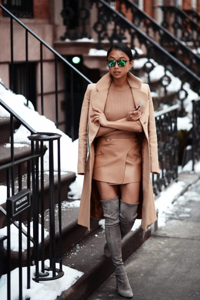Margaret Zhang Is Wearing Mirrored Sunglasses From Stella McCartney, Coat, Top And Skirt From Michael Kors, Thigh Highland Boots From Stuart Weitzman