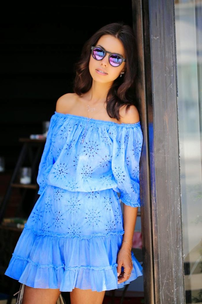 Annabelle Fleur is wearing a light blue off the shoulder dress from Sunday St. Tropez and sunglasses from Illesteva Leonard