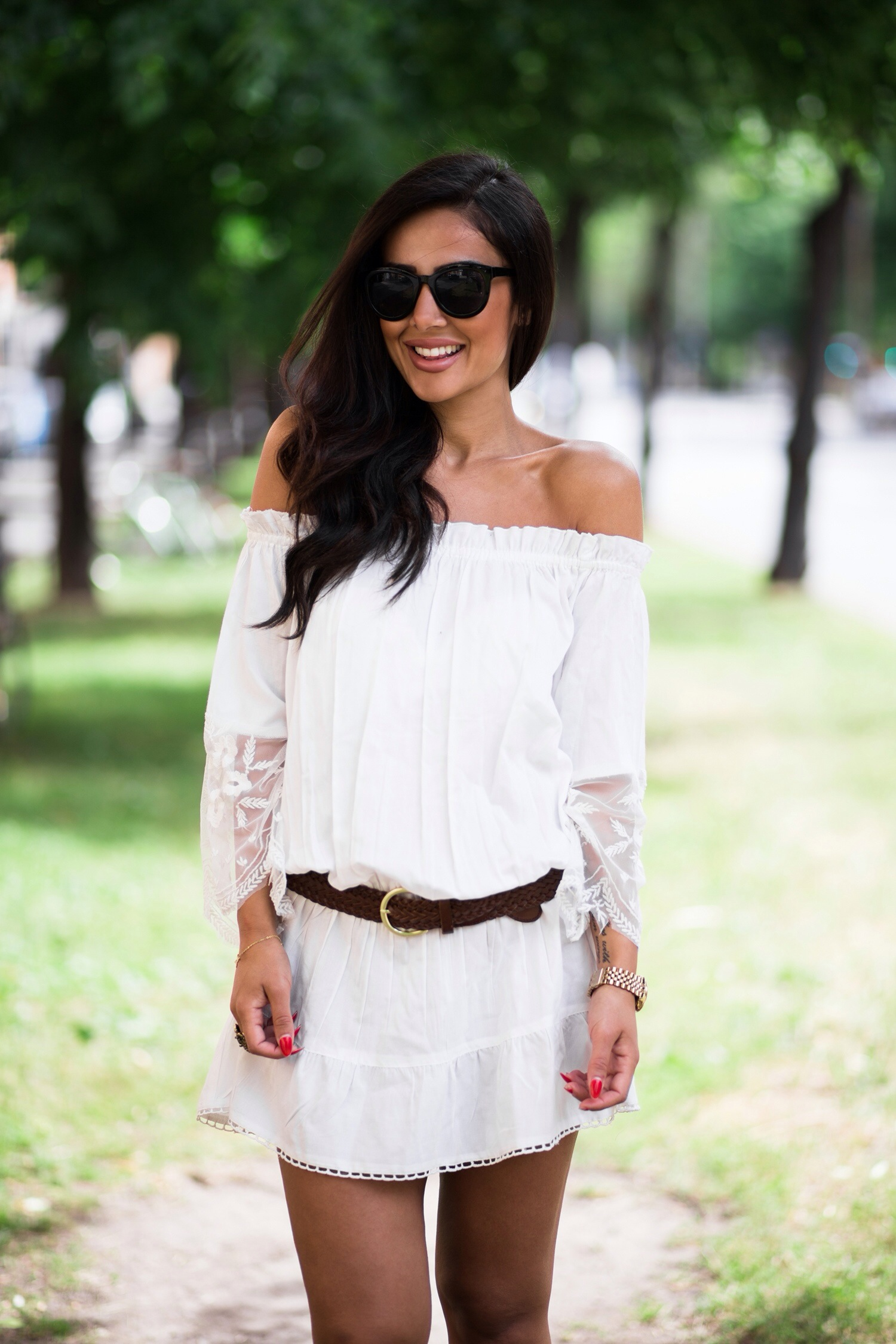 Sharareh Sophia is wearing a white off the shoulder lace trim dress from Gina Tricot, and sunglasses from BikBok