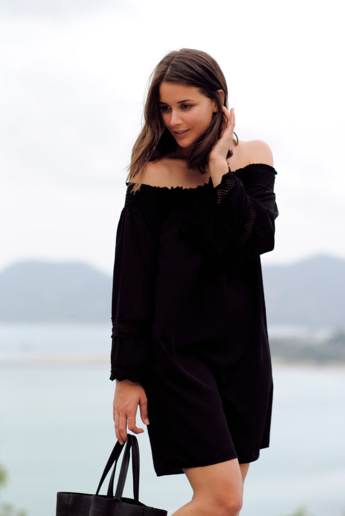 Sara Donaldson is wearing a black off the shoulder dress from Va Va