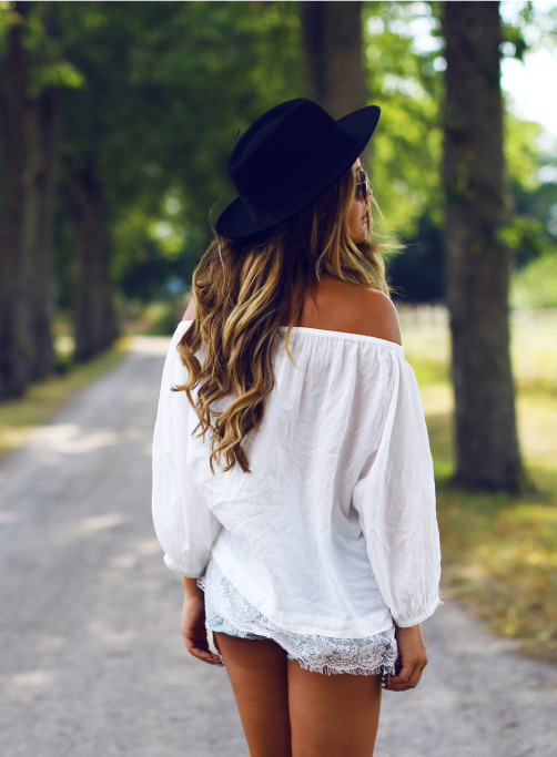 Angelica Blick is wearing a white off the shoulder tunic from Gina Tricot, shorts from Lev's and the hat is from Hattbaren