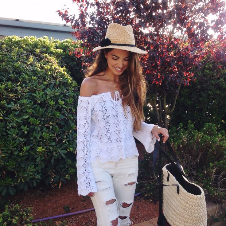 Negin Mirsalehi is wearing an off the shoulder mesh top, ripped white jeans and hat