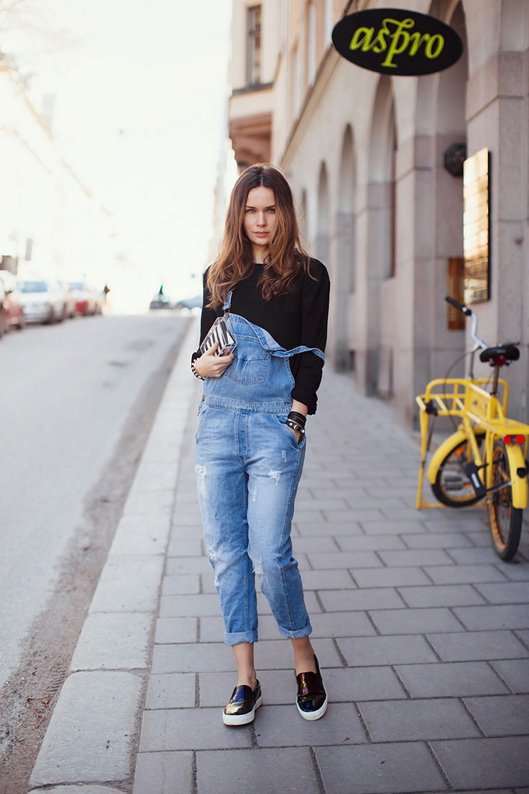 Caroline Blomst Is wearing denim overalls, black jumper and slip-ons