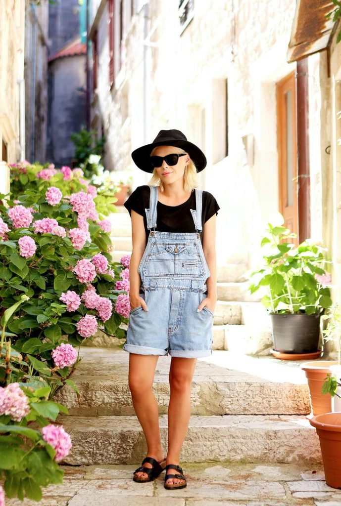 Jessie Bush is wearing a black fedora hat from ASOS, T-Shirt from APC, vintage overalls from Urban Outfitters, and Birkenstocks