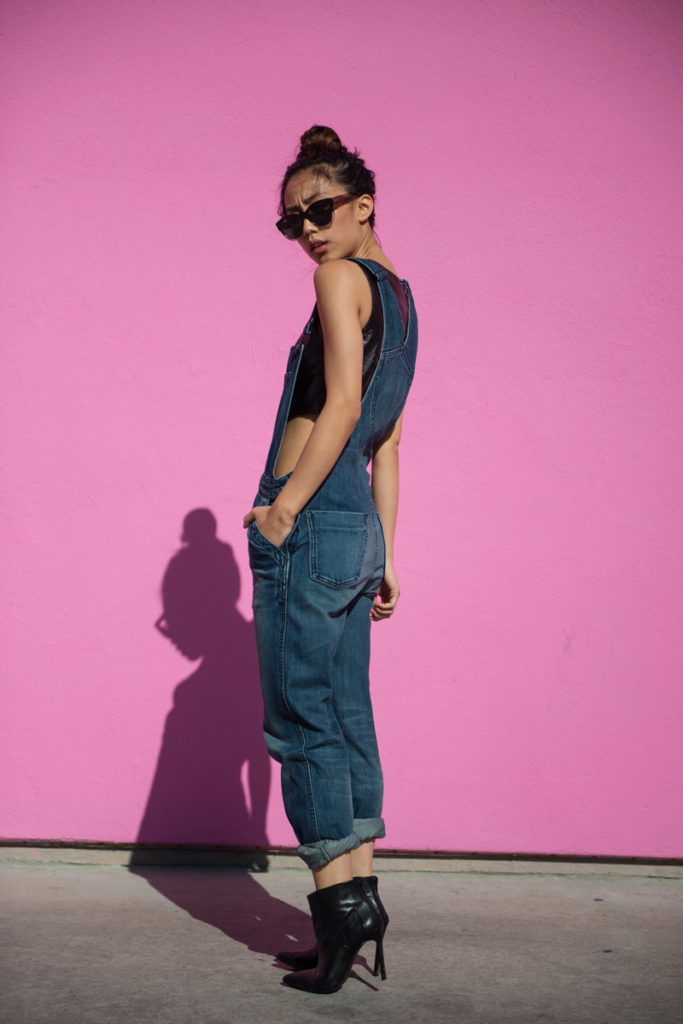 Jenny Ong Is Wearing Black Crop Top From Jaggar, Denim Overalls From Black Orchid, Boots From ShoeMint, And Sunglasses From Salt