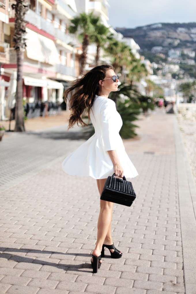 Audrey Leighton Rogers is wearing a white structured dress from Girissima, sunglasses from Zero UV, a vintage bag and black mules from Sonia de Nisco Raffia