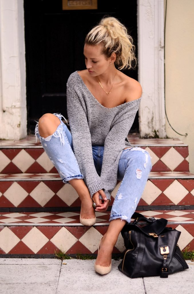 Anouk Yve is wearing an oversized knit off the shoulder top from Somewhere Elsewhere, jeans from Zara, shoes from Christian Louboutin and a bag from Chloe