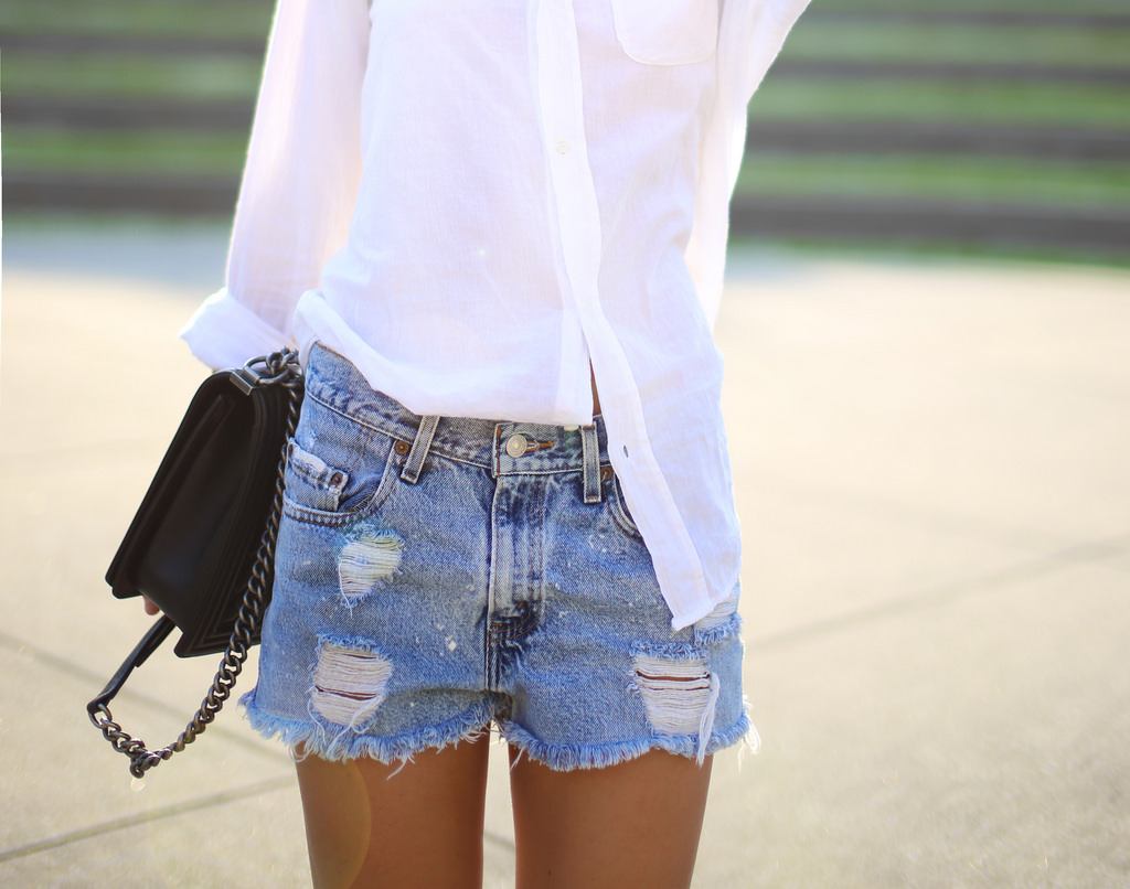 Mary Seng Is Wearing A Button Up Shirt From Current/Elliott And Ripped Denim Shorts From Levi's And A Bag From Chanel