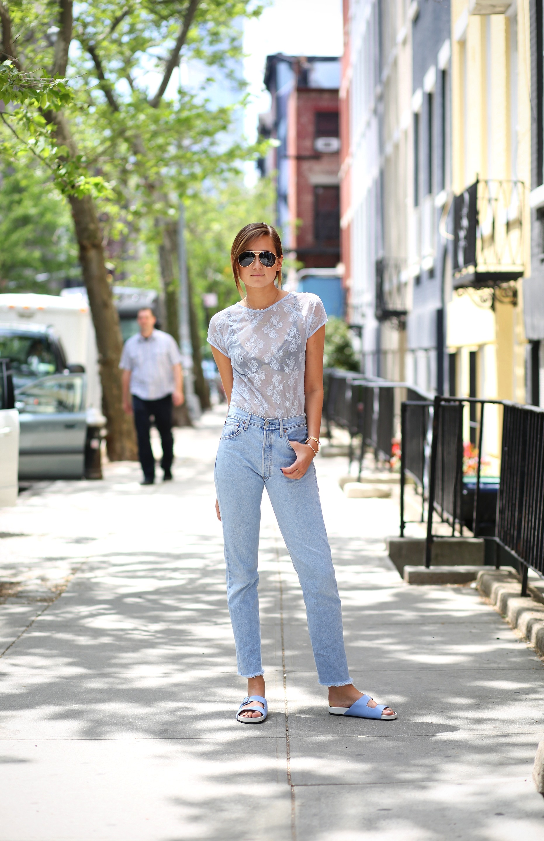 Danielle Bernstein is wearing a powder blue sheer vintage top, jeans from Current Elliot and slides from ASOS