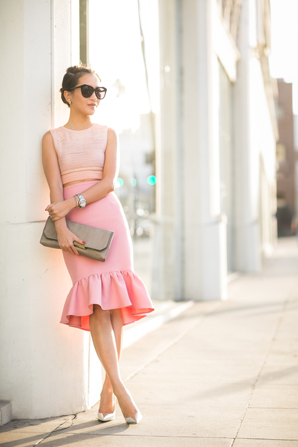 Wendy Nguyen is wearing Top from Jonathan Simkhai, pink peplum skirt from ASOS, Shoes from Jimmy Choo, Bag from J.Crew and sunglasses from Karen Walker