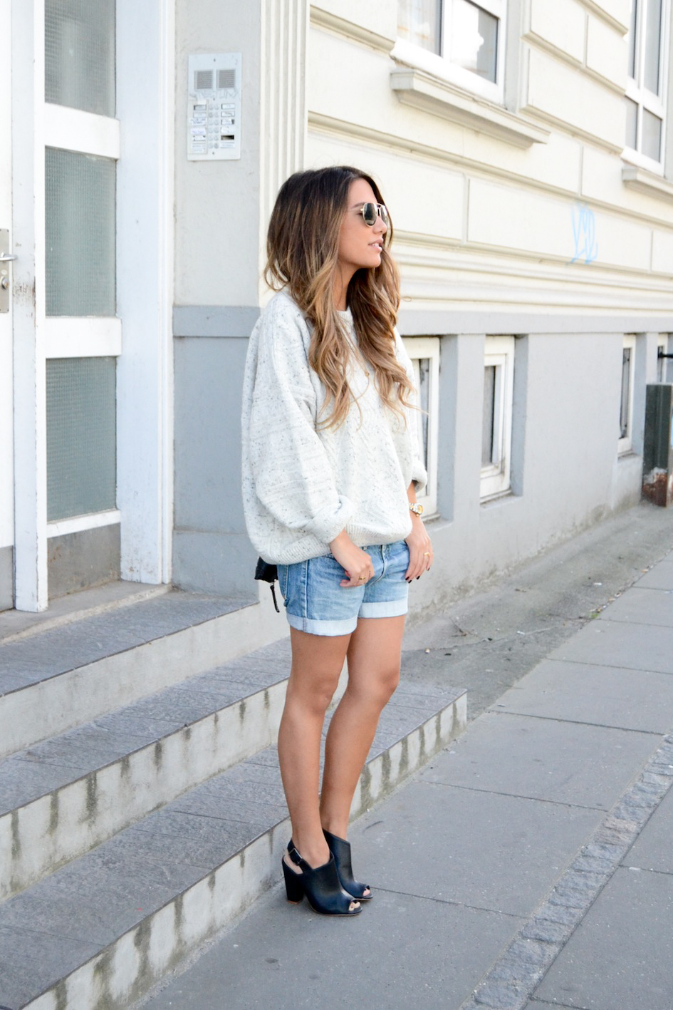 Michelle Nielsen is wearing an oversized beige jumper, denim shorts and mules from H&M