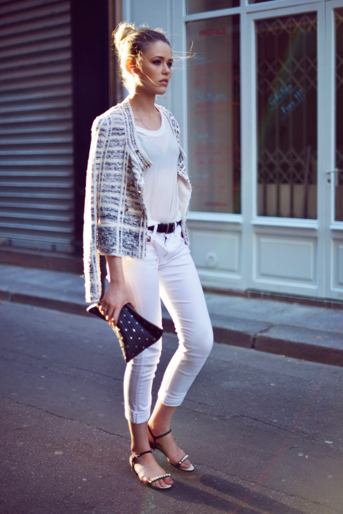 Krisitina Bazan is wearing a top from Lanvin, white jeans from Rag & Bone, jacekt and clutch from Sonia Rykiel, and shoes from Chanel