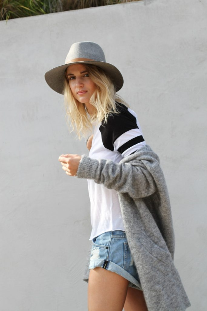 Mija is wearing grey mohair cardigan from Acne Studios, long sleeve baseball top from TopShop, denim shorts from One Teaspoon and a wool felt hat from Janessa Leone