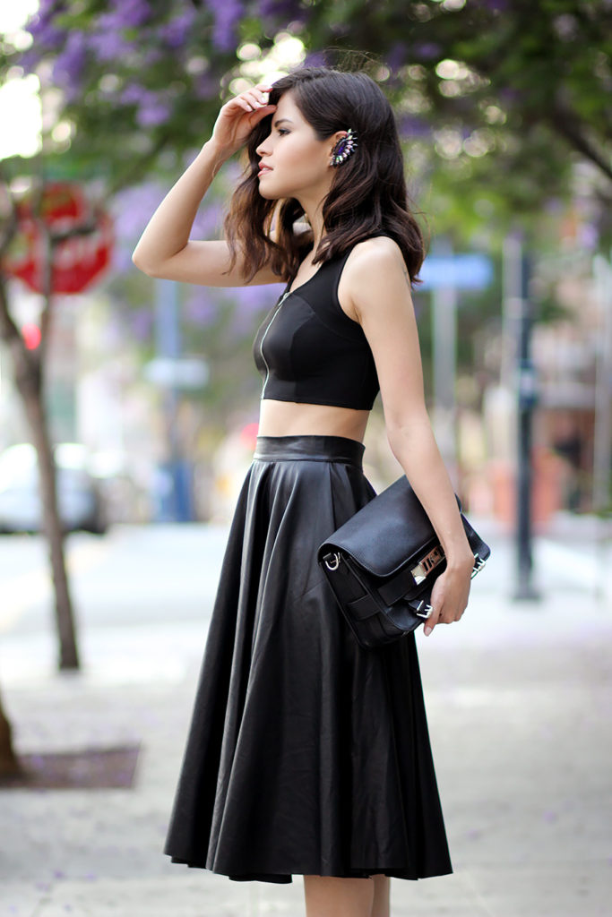 Adriana Gastellum is wearing a black zipper crop top from Topshop, black faux leather midi skirt and bag from Proenza Schouler