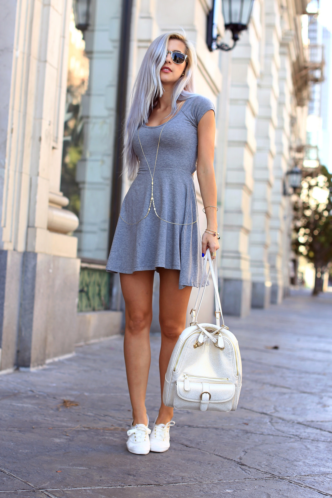 Evelina Barry Is Wearing A Grey Dress By Brandy Melville, A Backpack From Sorial, Shoes From Keds Bodychain And Sunglasses From Warby Parker