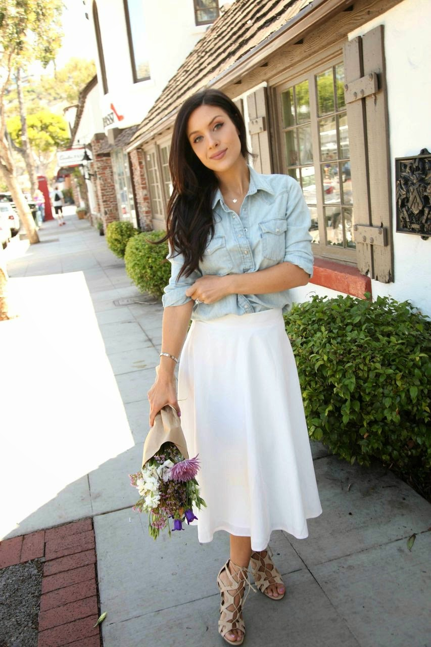 Andee Layne Is Wearing Faded Denim Shirt, White Midi Skirt From ASOS And Lace Up Sandals From Sam Edelman