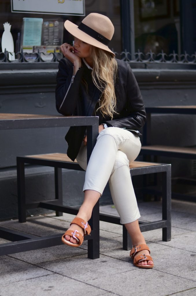 Anouk Yve Is Wearing Black Leather Jacket From Gat Rimon, White Leather Trousers From Ganni, Hat From the Kooples, Shirt From Acne And Sandals From Bimba Y Lola