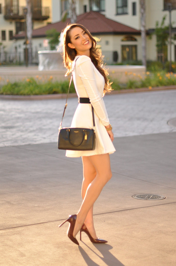Jessica Norcal Is Wearing A Simple White Skater Dress From MissGuided, Darl Brown Shoes From Ivanka Trump And A Bag From Coach