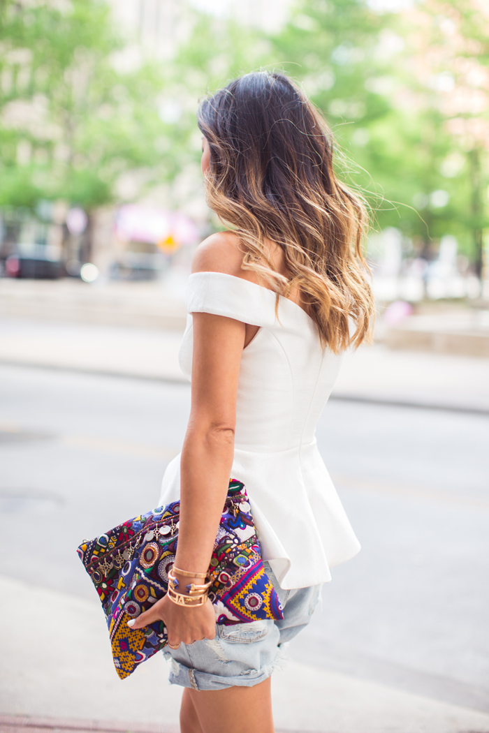 Song Of Style Is Wearing Off The Shoulder Top From Cameo, Distressed Denim Short From Res, And Multi Coloured Embroidered Clutch From Simone Camille