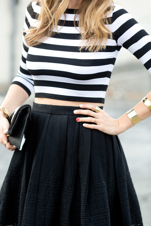 A House In The Hills Is Wearing A Black Eyelet Skirt From Tibi, Black And White Striped Crop Top From Bailey 44, And The Bag Is From Clare Vivier