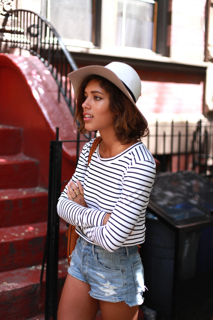 Christina Caradona is Wearing A Crop Top With Stripes From Burkhart, The Distressed Shorts Are From Citizens Of Humanity And The Hat Is From Supertrash