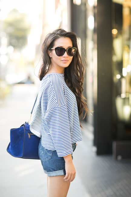 Wendy Nguyen is wearing a blue and white striped crop top from Townsen, denim shorts from AG Adriano Goldschmied and a blue bag from Celine