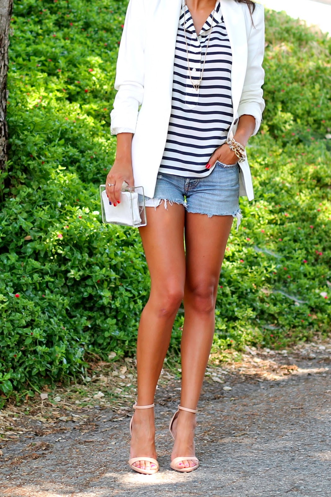 Pursuit Of Shoes is wearing a striped top from J. Crew, white blazer from Zara and clutch from Missguided